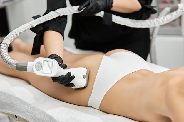 흰색 란제리의 여자 엉덩이에 내구 마사지를 사용하는 치료사