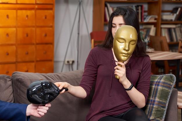 セラピストがセラピーセッション中に女性患者とプラスチックマスクを使用して