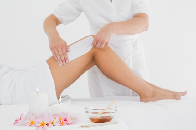 Therapist waxing woman's leg at spa center