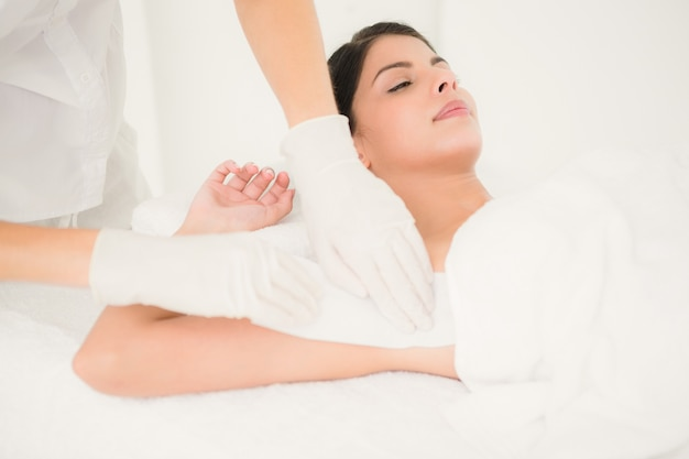 Therapist waxing womans axilla at spa center