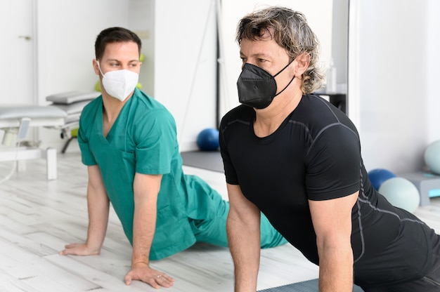 Therapist with protective face mask assisting patient with stretching exercises.