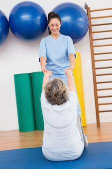Therapist working with senior woman on exercise mat