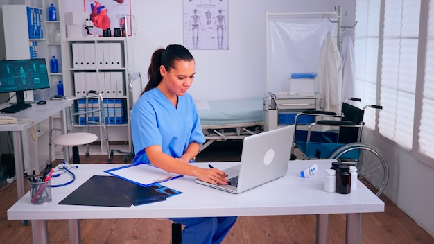 Therapist writing list of consulted patients online, making research, noting, taking useful information on clipboard. doctor assistant in uniform working on laptop in modern hospital office.