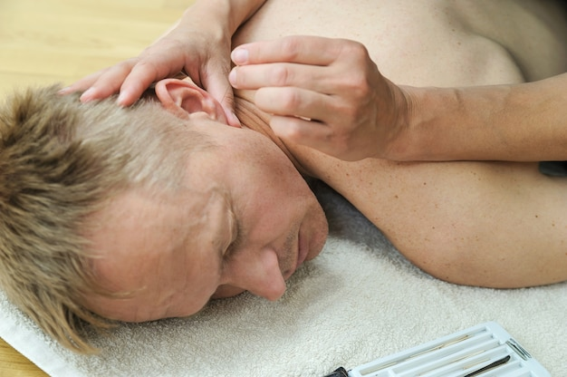 Therapt's hands are applying needles to acupuncture points on the patient's ear