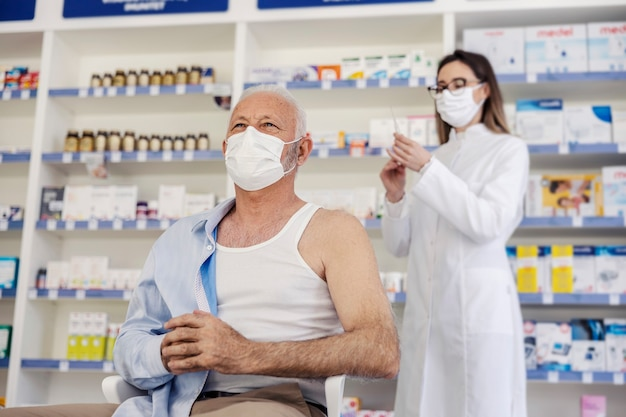 요양원 약국에서의 치료. 여성 약사는 의자에 앉아 셔츠를 벗고있는 노인에게 치료를 제공합니다. 예방 접종, 코로나 바이러스 속보
