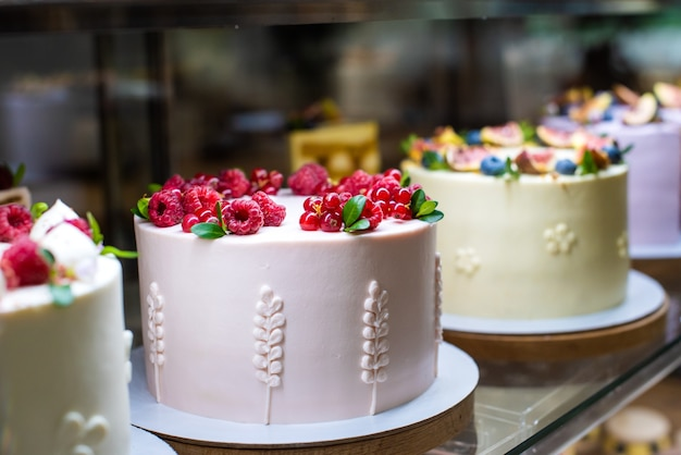 窓際にはたくさんのケーキが売られています。ベリーで飾られました。赤いラズベリーとスグリは、コンティド製品の明るい装飾です。