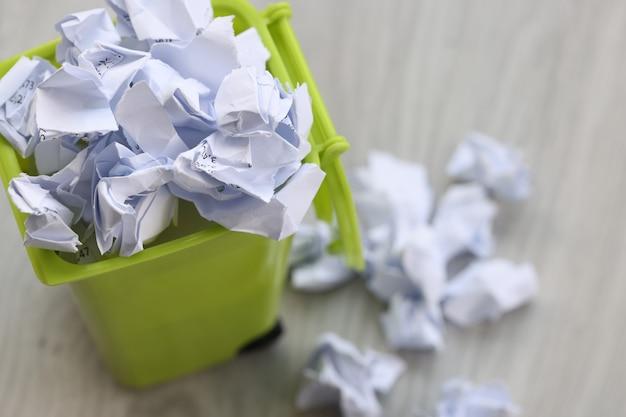 В зеленом мусорном ведре валяются скомканные клочки бумаги концепция переработки использованной бумаги