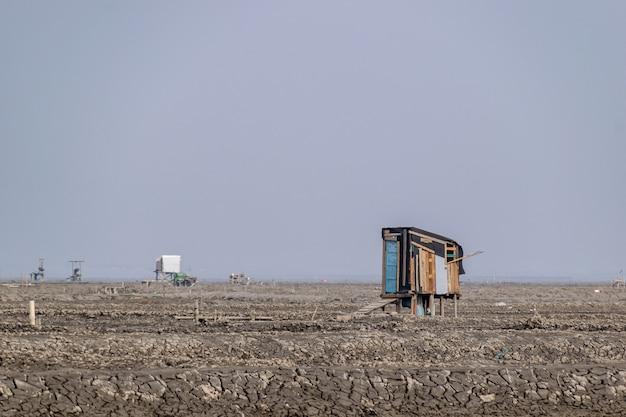 На темном пляже есть фермы и дороги из почвы.