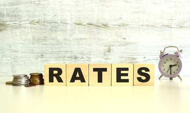 동전 옆 탁자 위에 글자가 있는 5개의 나무 큐브가 있습니다. rates 단어. 회색 배경에.