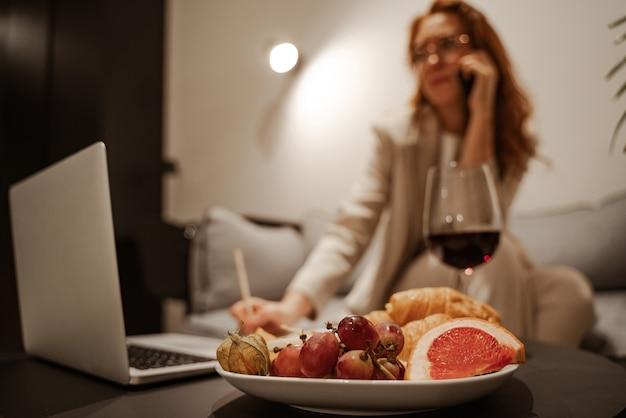 テーブルの上にはグラスワイン、クロワッサン、フルーツがあります。時間外労働。夜にソファに座って、ラップトップでリモートで作業しているスタイリッシュな若い実業家。出張観光。