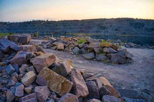 На территории старого затопленного каменного карьера в теплом вечернем свете видны большие груды валунов.