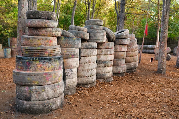 There are a lot of abandoned old and damaged tires at the base for playing paintball where players excited by the game are hiding