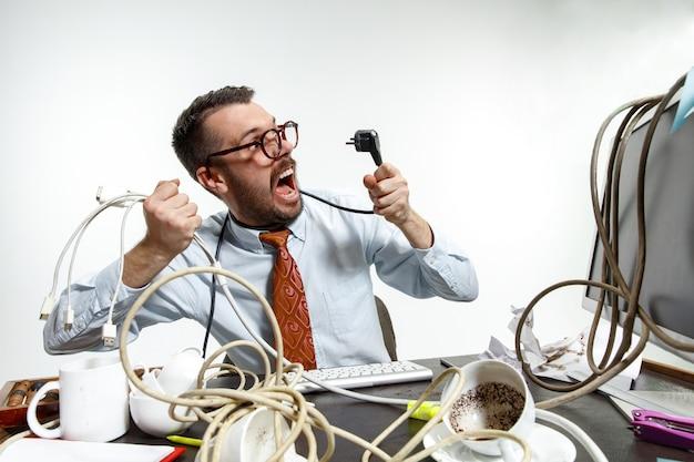 Ci sono molti fili sul posto di lavoro e l'uomo è costantemente aggrovigliato in essi