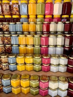 판매용 카운터에는 유기농 천연 꿀이 담긴 항아리가 많이 있습니다. 꿀 박람회에서 다양한 꿀, 플라스틱 캔의 다양한 색상을 판매할 준비가 되었습니다. 꿀이 가득한 견과류.