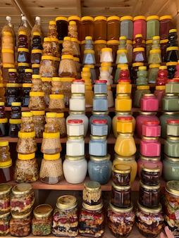 На прилавке есть много банок с органическим натуральным медом. на ярмарке меда продают разный мед, разные цвета в пластиковых банках. орехи с медом.