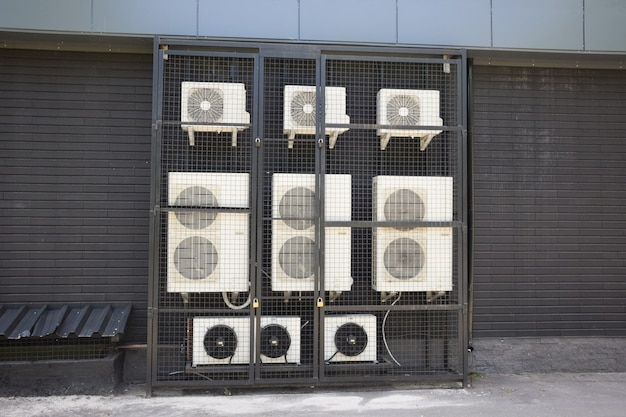 There are many operating air conditioners of different types and capacities near the wall of a store or office. for safety, they are closed with locks in a box made of iron mesh.