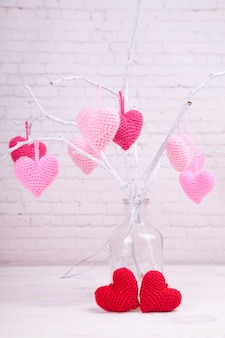 There are many pink knitted hearts on white branches. glass bottle. valentine's day.