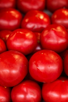 There are many ripe juicy red tomatoes on the market counter. health and vitamins from nature. close-up. vertical.