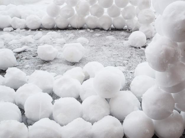 雪の中には丸い雪玉がたくさんあります。冬の楽しみ。抽象的な新年のクリスマスの背景。スペースをコピーします。