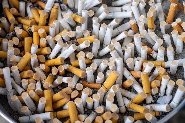 灰皿の砂の上には多くの種類のタバコのスタブがあります。タバコは健康に良くありません。