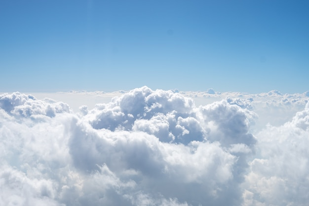 There are many white clouds among the blue sky. this view is from the window on airplane.