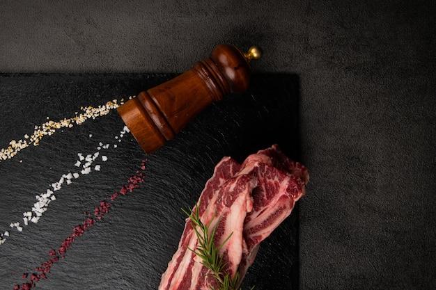 검은 도마에 생갈비칼과 소금, 후추가 있다