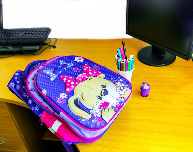 There are school supplies on the computer table
