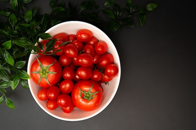 There are several tomatoes on a white plate its a black background