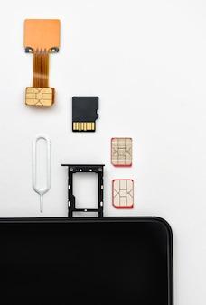 Simカード、メモリカード、空きスロットのあるスマートフォンの近くにピンがあります
