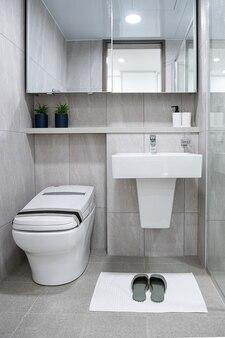 욕실에는 세면대와 거울 변기가 있고 바닥에는 수건과 슬리퍼가 있습니다.