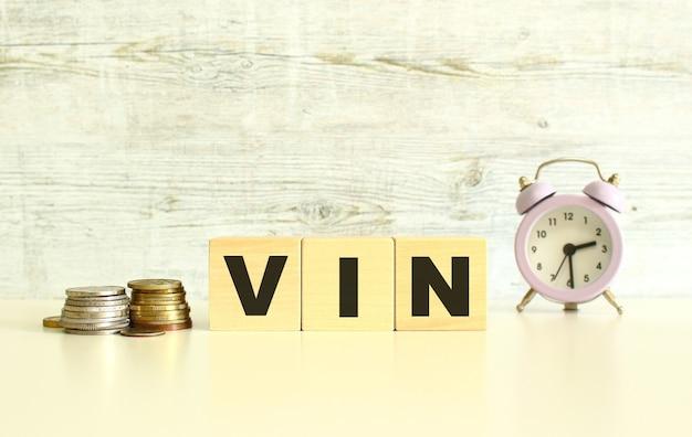 동전 옆 탁자 위에 글자가 있는 세 개의 나무 큐브가 있습니다. 단어 vin. 회색 배경에.