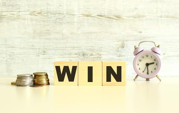 동전 옆 탁자 위에 글자가 있는 세 개의 나무 큐브가 있습니다. 단어 win입니다. 회색 배경에.