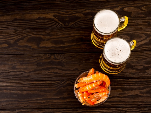 There are two glasses of light beer with shrimp on wooden background, top view