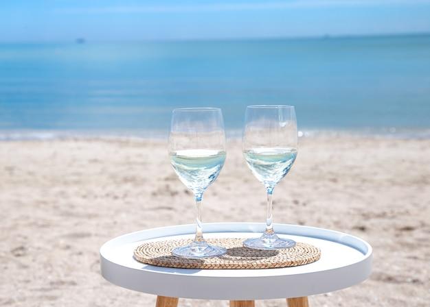 바다 옆 테이블에 샴페인 두 잔이 있습니다. 휴일의 개념.