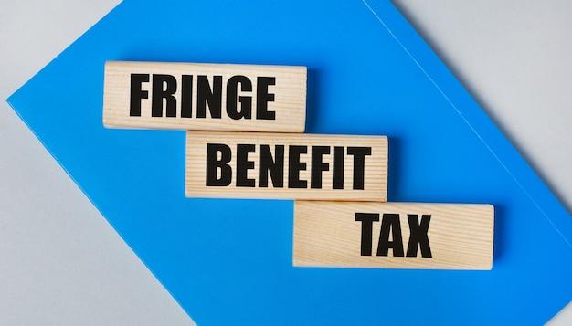 На светло-сером фоне находится блокнот синего цвета. выше три деревянных блока с надписью fringe benefit tax.