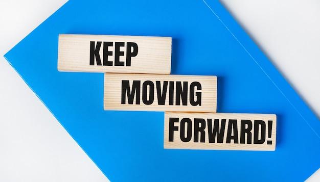 На светло-сером фоне находится блокнот синего цвета. выше три деревянных блока со словами продолжайте двигаться вперед.