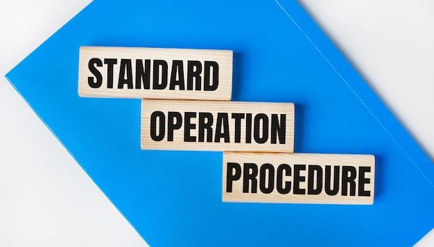 На светло-сером фоне находится блокнот синего цвета. выше три деревянных блока с надписью стандартная процедура эксплуатации.