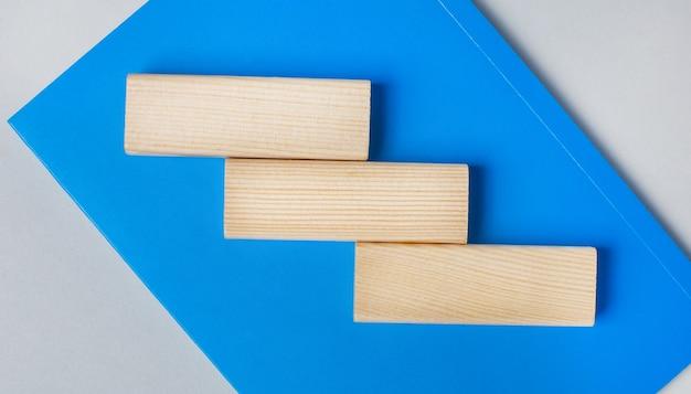 明るい灰色の背景に青いノートがあります。上部には、テキストを挿入するためのスペースがある3つの木製の空白のブロックがあります。テンプレート。コピースペース