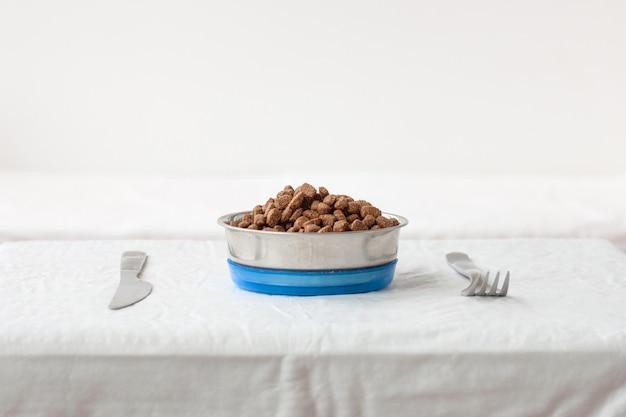 На столе рядом с ножом и вилкой стоит миска с собачьим кормом. концепция корма для кошек, собак, животных.