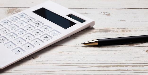 На светлом деревянном столе лежат калькулятор и ручка. крупный план на рабочем месте. бизнес-концепция