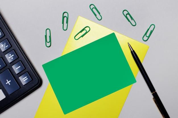 灰色の背景に電卓、緑色のペーパークリップ、黄色のシートにテキストやイラストを挿入するための緑色のカードがあります。テンプレート。フラットレイ