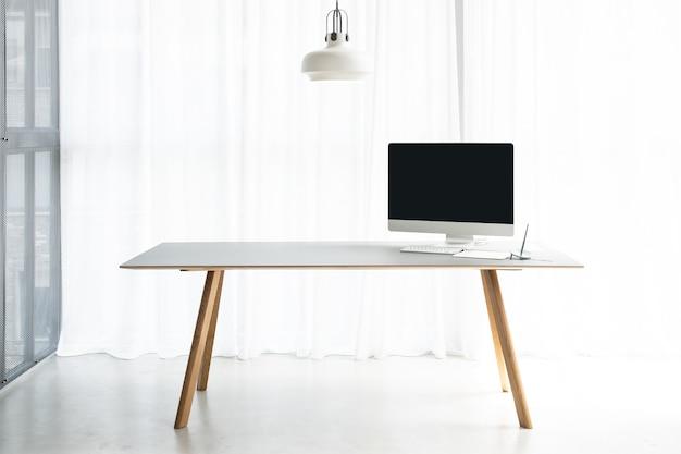 На столе в офисе компьютер и ручка.