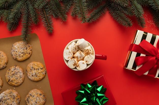 На столе чашка горячего шоколада и рождественское печенье.