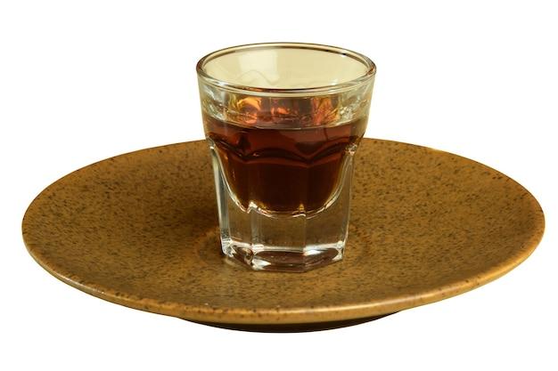 白い背景の茶色のセラミック受け皿にコニャックのガラスがあります。クローズアップ写真。