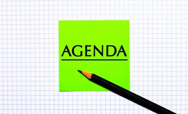 市松模様の紙に「agenda」と書かれた緑色のステッカーと黒い鉛筆があります。