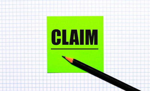 市松模様の紙に「claim」と書かれた緑色のステッカーと黒い鉛筆があります。