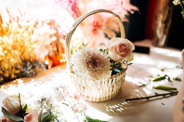 꽃집 나무 탁자 위에 흰 모란과 장미가 든 작은 흰색 바구니가 있습니다.
