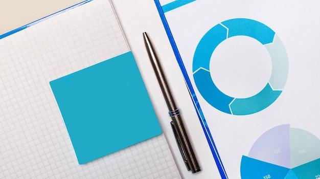 青いノートステッカーと青いグラフの間にペンがあります。ビジネスコンセプト