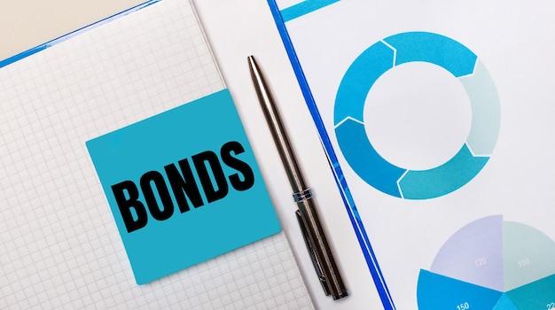 Bonds 텍스트가있는 파란색 스티커 메모와 파란색 차트 사이에 펜이 있습니다. 비즈니스 개념. 위에서보기
