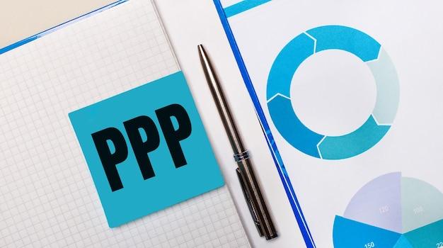 Между синей запиской с текстом ppp paycheck protection program и синей таблицей находится ручка. бизнес-концепция. вид сверху